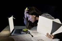 Giovane ragazza disperata dello studente universitario nello sforzo per esame che studia tardi con i libri ed il computer portati Immagini Stock Libere da Diritti