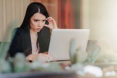Giovane ragazza emozionale attraente in vestiti stile affare che si siedono ad uno scrittorio su un computer portatile e su un te immagine stock