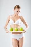 Giovane ragazza esile che tiene una mela verde Fotografie Stock Libere da Diritti