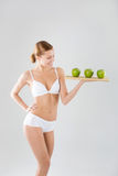 Giovane ragazza esile che tiene una mela verde Fotografie Stock