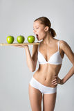 Giovane ragazza esile che tiene una mela verde Immagini Stock Libere da Diritti