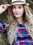 Giovane ragazza favorita bionda del paese in cappello vicino ai mucchi di fieno immagini stock libere da diritti