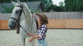 Giovane ragazza felice che sorride e che accarezza il suo cavallo bianco grazioso sull'area 4K stock footage