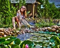 Giovane ragazza felice con lo streamlet del giardino vicino allo stagno Immagini Stock