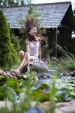 Giovane ragazza felice con lo streamlet del giardino vicino allo stagno Fotografia Stock