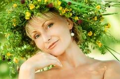 Giovane ragazza felice in corona delle erbe e dei fiori Giorno di estate in un prato fotografie stock