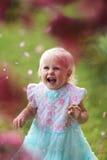 Giovane ragazza felice del bambino che ride come caduta dei petali del fiore fuori da un Cr fotografie stock libere da diritti