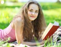 Giovane ragazza felice del ritratto che legge un libro che si trova in un parco Immagine Stock Libera da Diritti
