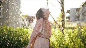 Giovane ragazza felice divertendosi sotto la pioggia Sorriso bagnato sorridente del bambino ed avere buon umore all'aperto archivi video