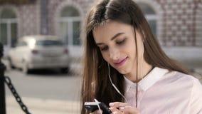 Giovane ragazza graziosa alla moda con il telefono che posa nelle vie della città Modello teenager con le cuffie archivi video