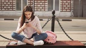 Giovane ragazza graziosa alla moda con il telefono che posa nelle vie della città Modello teenager con le cuffie stock footage