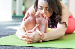 Giovane ragazza graziosa che allunga le gambe Allenamento di yoga Immagine Stock Libera da Diritti