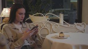 Giovane ragazza graziosa che prende le foto sullo smartphone del dolce da acquolina in bocca fresco con le decorazioni sulla tavo video d archivio