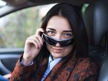 Giovane ragazza graziosa che si siede dietro la ruota di un'automobile Fotografia Stock Libera da Diritti
