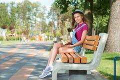 Giovane ragazza graziosa che si siede sul banco che tiene un libro Fotografie Stock