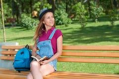 Giovane ragazza graziosa che si siede sul banco che tiene un libro Fotografia Stock Libera da Diritti