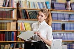 Giovane ragazza graziosa con il computer portatile che posa alla macchina fotografica nella biblioteca Immagine Stock Libera da Diritti