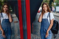 Giovane ragazza graziosa con la passeggiata della cartella sulla riflessione urbana della via immagini stock libere da diritti