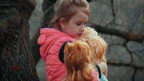 Giovane ragazza graziosa con le bambole sole nel legno stock footage