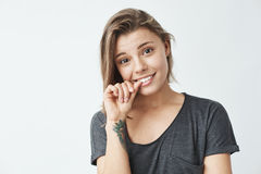 Giovane ragazza graziosa nervosa che esamina le unghie mordaci della macchina fotografica sopra fondo bianco Fotografia Stock Libera da Diritti
