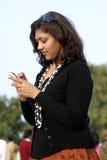 Giovane ragazza indiana che per mezzo del telefono mobile Fotografia Stock