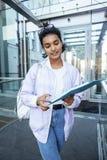 Giovane ragazza indiana moderna sveglia alla costruzione dell'università che si siede sulle scale che legge un libro, vetri d'uso Fotografia Stock Libera da Diritti