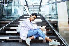 Giovane ragazza indiana moderna sveglia alla costruzione dell'università che si siede sulle scale che legge un libro, vetri d'uso Immagine Stock