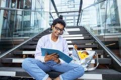 Giovane ragazza indiana sveglia alla costruzione dell'università che si siede sulle scale che legge un libro, vetri d'uso dei pan Fotografie Stock