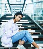 Giovane ragazza indiana sveglia alla costruzione dell'universit? che si siede sulle scale che legge un libro, vetri d'uso dei pan fotografia stock
