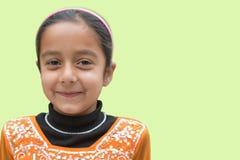 Giovane ragazza indiana sveglia con la posa sorridente sul contesto verde molle, ampio spazio vuoto per testo immagini stock libere da diritti