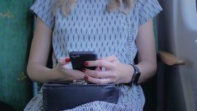 Giovane ragazza irriconoscibile con i bei chiodi rossi, sedentesi nel sedile di un aeroplano, di un treno o di un bus Usa un cell video d archivio