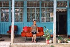 giovane ragazza locale del villaggio che ha un resto durante il pomeriggio davanti alla loro montagna tradizionale fotografie stock