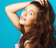Giovane ragazza moderna adolescente graziosa che posa felice emozionale su fondo blu, concetto della gente di stile di vita fotografia stock