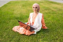 Giovane ragazza musulmana che per mezzo del computer portatile Fotografie Stock Libere da Diritti