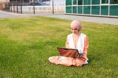 Giovane ragazza musulmana che per mezzo del computer portatile Fotografia Stock Libera da Diritti