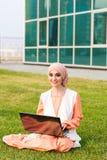 Giovane ragazza musulmana che per mezzo del computer portatile Immagine Stock
