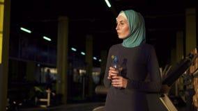 Giovane ragazza musulmana sportiva in acqua potabile del hijab dalla bottiglia dopo l'allenamento archivi video