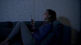 Giovane ragazza o donna felice dell'adolescente sul suo 20s che si trova su felice a tarda notte dello strato domestico facendo u video d archivio