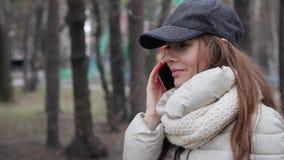 Giovane ragazza piacevole che porta tazza grigia e camice che parlano sul cellulare nel parco di primavera archivi video