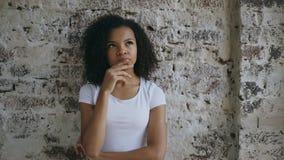 Giovane ragazza premurosa della corsa mista che pensa a risolvere problema sul fondo del muro di mattoni Fotografia Stock