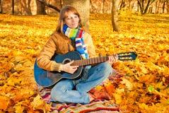 Giovane ragazza romantica nella sosta di autunno con la chitarra Fotografie Stock