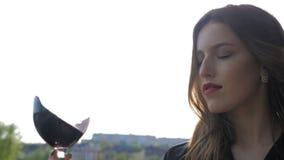 Giovane ragazza sexy con le labbra rosse che girano un vetro di vino rosso sul fondo della natura archivi video