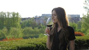 Giovane ragazza sexy con le labbra rosse che girano un vetro di vino rosso sul fondo della natura stock footage