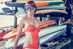 Giovane ragazza in costume da bagno rosso - surfista con il bordo di spuma che posa sulla spiaggia del DUA di Nusa, isola tr Fotografie Stock Libere da Diritti