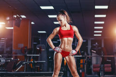 Giovane ragazza sexy di atletica che riposa dopo gli esercizi di allenamento di forma fisica in palestra immagine stock