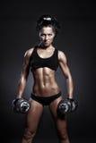 giovane ragazza sexy di forma fisica che fa allenamento con le teste di legno sopra fondo nero Immagine Stock