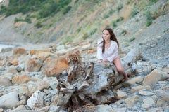 Giovane ragazza sexy di hippy nello stile di eleganza di boho che posa su un albero asciutto enorme sui precedenti delle rocce immagine stock libera da diritti