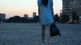 Giovane ragazza snella in un vestito che tiene uno zaino e che cammina giù la via nella sera archivi video