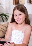 Giovane ragazza sorridente che lo esamina in salone Immagine Stock
