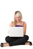 Giovane ragazza sorridente con il computer portatile Immagini Stock